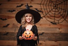 Halloween Witch concept - little caucasian witch child enjoy with halloween candy pumpkin jar. over bat and spider web background. Royalty Free Stock Images