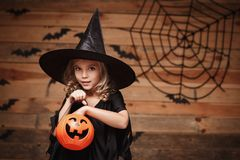 Halloween Witch concept - little caucasian witch child enjoy with halloween candy pumpkin jar. over bat and spider web background. Royalty Free Stock Image