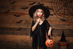 Halloween Witch concept - little witch child with halloween sweet and candy with cheerful smiling. over bat and spider web backgro royalty free stock image