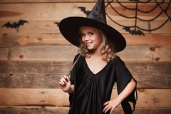 Halloween Witch concept - little witch child enjoy playing with magic wand. over bat and spider web background. Stock Images