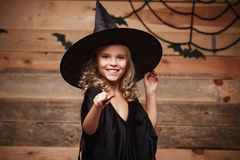 Halloween Witch concept - little witch child enjoy playing with magic wand. over bat and spider web background. Stock Photography