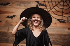 Halloween Witch concept - little witch child enjoy playing with magic wand. over bat and spider web background. Royalty Free Stock Photos