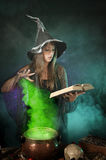 Halloween witch cooking a potion in a cauldron Royalty Free Stock Image
