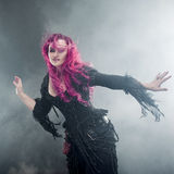 Halloween Witch creates magic. Attractive woman with red hair in witches costume Royalty Free Stock Images