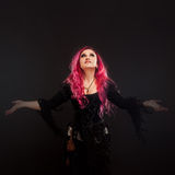 Halloween Witch creates magic. Attractive woman with red hair in witches costume standing outstretched arms Stock Image