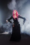 Halloween Witch creates magic. Attractive woman with red hair in witches costume standing outstretched arms, strong wind Royalty Free Stock Photos