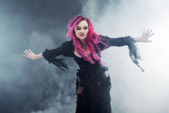 Halloween Witch creates magic. Attractive woman with red hair in witches costume standing outstretched arms, strong wind Royalty Free Stock Images