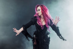 Halloween Witch creates magic. Attractive woman with red hair in witches costume standing outstretched arms, strong wind Stock Photography