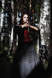 Halloween Witch in a dark forest. Beautiful young woman in witches costume . Halloween art design. Horror Background For Halloween Stock Photography