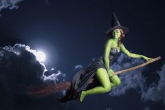 Halloween witch flying on broomstick Stock Photos