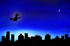 Halloween Witch flying over City Stock Images
