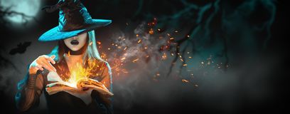 Halloween Witch girl with magic Book of spells portrait. Beautiful young woman in witches hat conjuring, making witchcraft