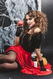 Halloween witch girl sitting on the floor with black wall and spider web on background. Holding pomegranate Stock Image