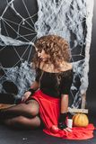 Halloween witch girl sitting on the floor with black wall and spider web on background. Looking down Stock Photo