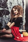 Halloween witch girl sitting on the floor with black wall and spider web on background. Put her hands to the knees. Royalty Free Stock Photography