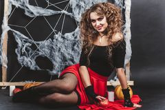 Halloween witch girl sitting on the floor with black wall and spider web on background. Wears a blouse and red skirt. Stock Photos