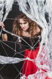 Halloween witch girl standing behind spider web in a blouse and red skirt. stock images