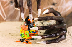 Halloween witch hands and colorful candies Royalty Free Stock Image
