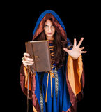 Halloween witch holding magical book of spells making magic. Beautiful young halloween witch wearing vintage gothic dress with hood holding magical book of Royalty Free Stock Photo