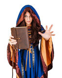 Halloween witch holding magical book of spells making magic. Beautiful young halloween witch wearing vintage gothic dress with hood holding magical book of Stock Photo