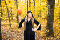 Halloween witch holding a orange pumpkin Stock Photos