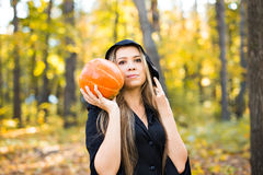 Halloween witch holding a orange pumpkin Royalty Free Stock Photo