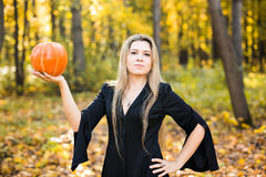 Halloween witch holding a orange pumpkin Stock Images