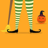 Halloween witch legs broom and pumpkin background Royalty Free Stock Photos