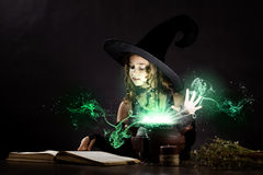 Halloween witch. Little Halloween witch reading conjure above pot Royalty Free Stock Photo