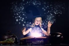 Halloween witch. Little Halloween witch reading conjure above pot Royalty Free Stock Photos