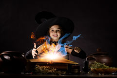 Halloween witch. Little Halloween witch reading conjure above pot Royalty Free Stock Photography