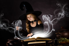 Halloween witch. Little Halloween witch reading conjure above pot Royalty Free Stock Images