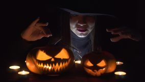 Halloween Witch with a magic Pumpkin. Beautiful young woman in witches hat and costume holding carved pumpkin. stock footage