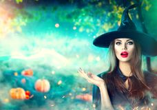 Halloween witch pointing hand over dark magic field with pumpkins Royalty Free Stock Photography