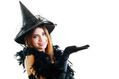 Halloween witch. Pretty young happy woman smiling and dressed as a fairy or witch for halloween party show open palm with copyspace Stock Photo