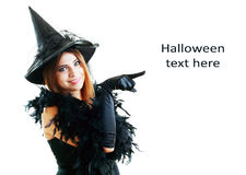 Halloween witch. Pretty young happy woman smiling and dressed as a fairy or witch for halloween party show point finger to copyspace Stock Photo