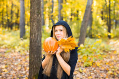 Halloween Witch with Pumpkin in a forest. Royalty Free Stock Images