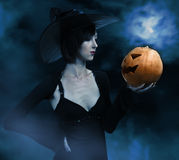 Halloween witch with a pumpkin royalty free stock images