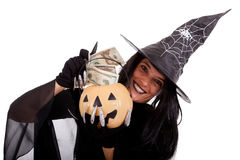 Halloween witch saving money. On her pumpkin stock photos