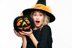 Halloween Witch with shocked expression holding a Jack o Lantern. Beautiful young woman in witches hat and costume holding pumpkin. Over white background royalty free stock images