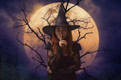 Halloween mystery concept. Halloween witch showing silence sign with finger over lips standing over dead tree, full moon and spooky cloudy sky, Halloween mystery stock image