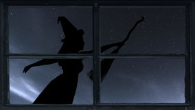 Halloween witch silhouette flying with broomstick. Window view. Stock Photos