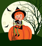 Halloween witch sitting on a pumpkin Stock Photography