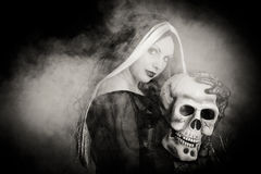 Halloween witch with a skull. Over black background with smoke. Black and white Royalty Free Stock Photo