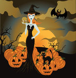 Halloween witch standing with skull and pumpkin Royalty Free Stock Photos