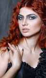 Halloween, witch, vampire. Red-haired vampire girl with red lips posing in urban twilight Royalty Free Stock Photos