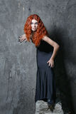 Halloween, witch, vampire. Red-haired vampire girl with red lips posing in urban twilight Royalty Free Stock Photo