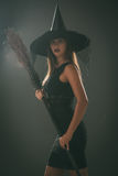 Halloween Witch. Young woman dressed like a witch. She is in dark clothing and holding a broom. Looking at camera Stock Photography
