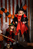 Halloween witches in costumes with broom. Halloween scene with two attractive witches, young mother and little daughter, in costumes and hats in black and red royalty free stock photo