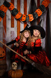 Halloween witches in costumes with broom. Halloween scene with two attractive witches, young mother and little daughter, in costumes and hats in black and red royalty free stock photography